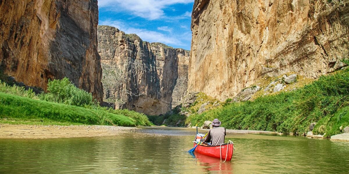 Man in a red canoe paddling down the river in between large cliffs