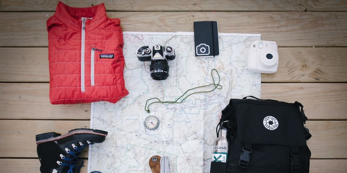 A jacket, camera, compass, backpack, and other objects laying atop a map