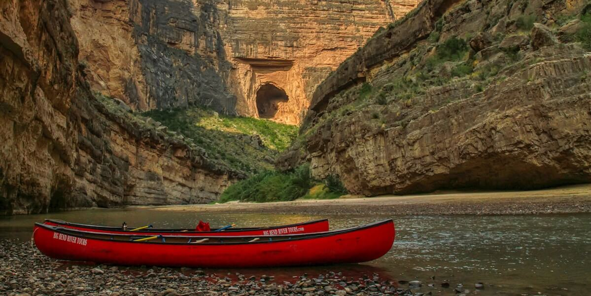 red canoes with calm river and canyon in background