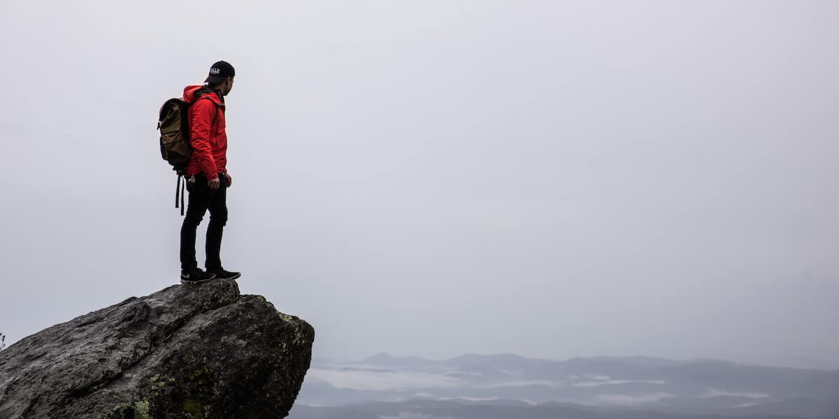 man on ledge overlooking mountain range in red jacket