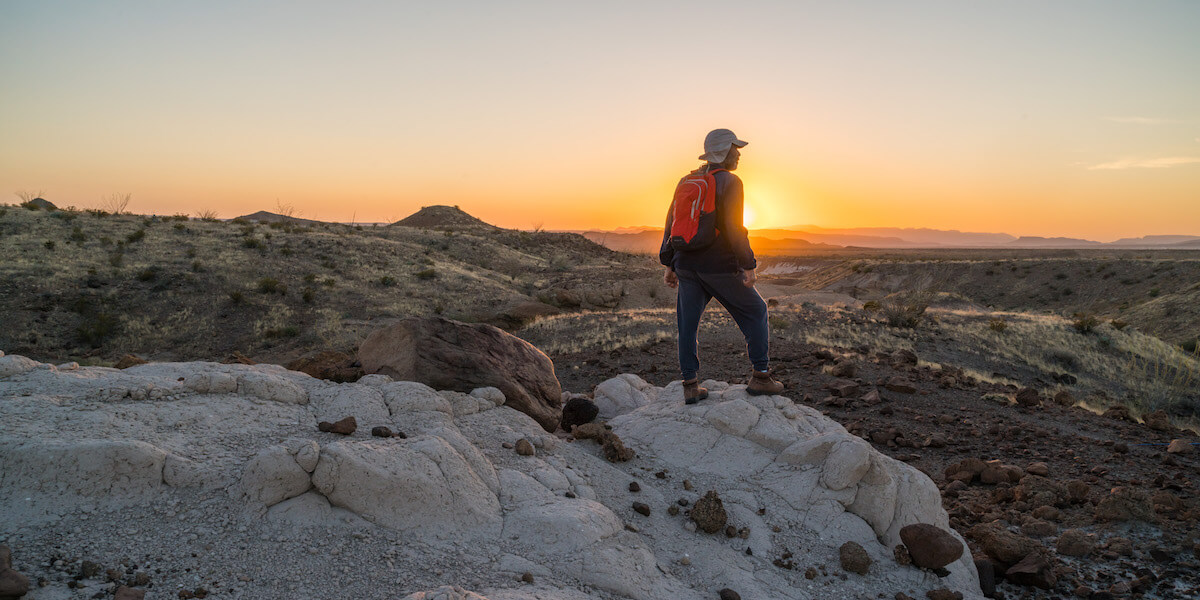 man with red backpack standing on ledge overlooking national park at sunset